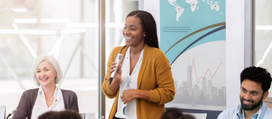 Confident young African American woman facilitates a panel discussion during a business conference or seminar.